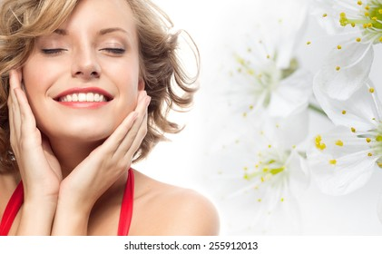 closeup portrait of attractive  caucasian smiling woman blond isolated on white studio shot lips toothy smile face hair head and shoulders looking at camera eyes closed spring flowers
