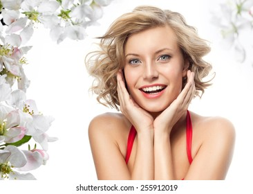 closeup portrait of attractive  caucasian smiling woman blond isolated on white studio shot lips toothy smile face hair head and shoulders looking at camera blue eyes tooth spring flowers