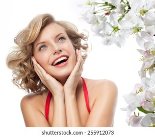 closeup portrait of attractive  caucasian smiling woman blond isolated on white studio shot lips toothy smile face hair head and shoulders looking up blue eyes tooth spring flowers