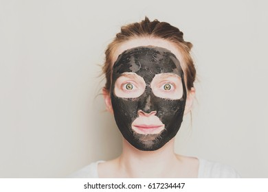 Close-up portrait of attractive girl with a black mask on the face. Skin care.