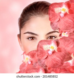 Closeup portrait of attractive girl cover part of face with fresh orchid flowers, isolated on pink background, luxury spa salon, wellness concept