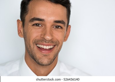 Close-up portrait of attractive happy man laughing. Isolated on gray background. Man with healthy teeth. Dental care.