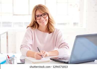 Close-up portrait of attractive middle aged businesswoman sitting in front of her laptop and writing something while working in the office.