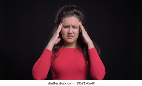 Closeup portrait of attractive middle-aged caucasian female having a headache in front of the camera with background isolated on black