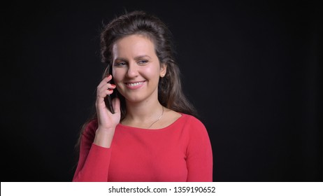 Closeup portrait of attractive middle-aged caucasian having a casual conversation on the phone and smiling in front of the camera