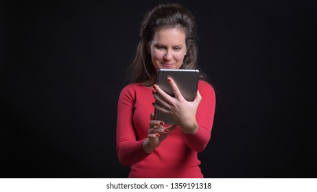 Closeup portrait of attractive middle-aged caucasian using the tablet with background isolated on black