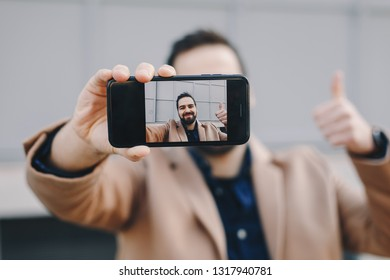 Close-up portrait of attractive and modern young man taking a selfie with his mobile phone, wearing fashionable clothes and posing for friends on social media. Focus on smartphone screen.