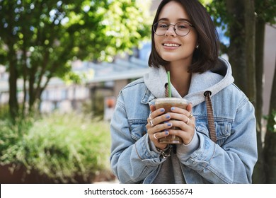 Close-up portrait of attractive smiling happy girl walking alone in park, enjoying drinking ice latte coffee, waiting for friend after classes, trying enjoy every moment of student life