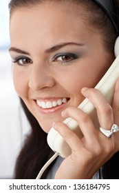 Closeup portrait of attractive smiling woman on phone call.