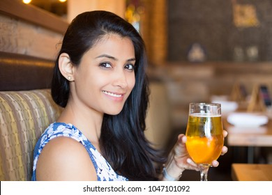 Closeup portrait, attractive woman enjoying beer inside bar, isolated indoors dining background