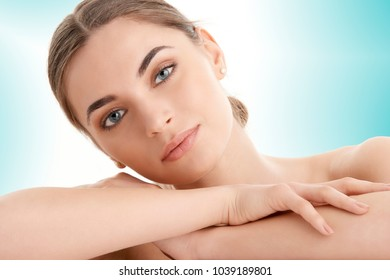 Close-up portrait of an attractive woman with perfect skin looking at camera while posing against at isolated light blue background.