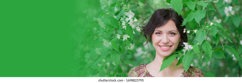 Closeup portrait of attractive woman in spring garden. Beautiful girl in spring landscape background. Springtime. Cover face healthy skin. Beauty clinic skincare organic natural spring concept banner