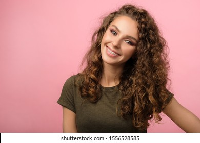 Closeup portrait of attractive young female with curly hair and pretty smile wearing dental braces isolated on pink background