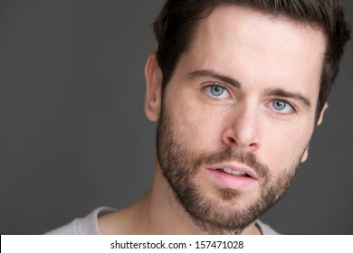 Closeup portrait of an attractive young man with blue eyes and beard