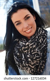 Closeup portrait of attractive young woman wearing scarf, smiling.