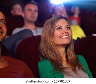 Closeup portrait of attractive young woman in cinema, watching movie, smiling.