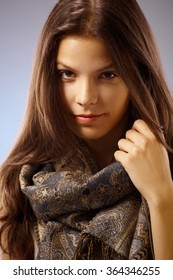 Closeup portrait of attractive young woman wearing scarf, looking at camera.