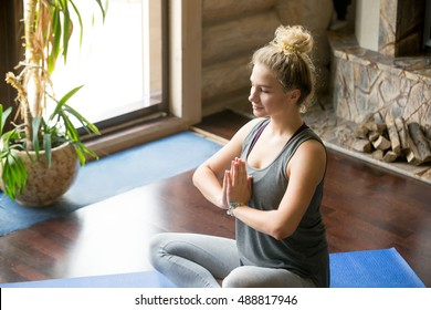 Close-up portrait of attractive young woman working out at home, doing yoga exercise on blue mat, sitting in Easy (Decent, Pleasant Posture) with palms in Namaste, meditating, breathing, relaxing