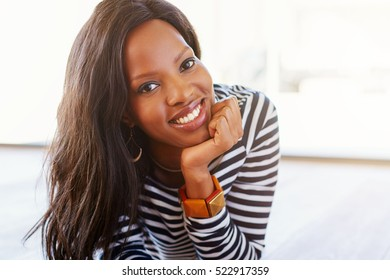 Closeup portrait of an attractive young woman smiling while lying on a wooden floor at home