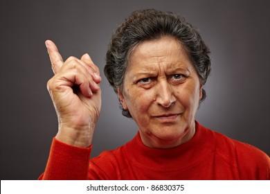 Closeup portrait of an authoritarian senior woman on gray background