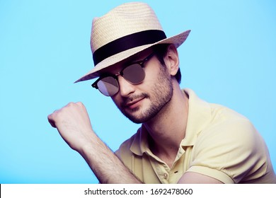 Closeup portrait of awesome hipster wearing fedora hat with intense look at camera. Headshot over blue studio background