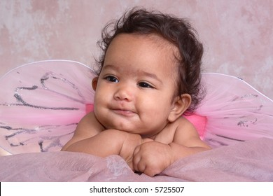 A close-up portrait of a baby with pink fairy wings
