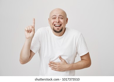 Close-up portrait of bald bearded guy pointing up and holding hand on belly while laughing out loud and lifting eyebrows, standing against gray background. Man with mates recall their adventure