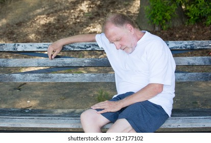 Closeup portrait bald old man in white shirt, blue shorts, exhausted, resting on a bench, looking down, trying to take a power nap, isolated outdoor outside background