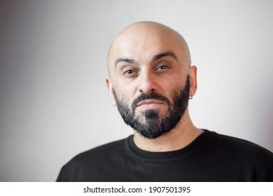 Close-up portrait of bearded bald man. White background