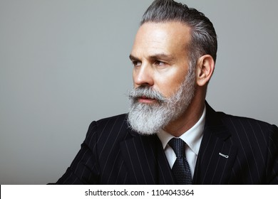 Close-up portrait of bearded gentleman wearing trendy suit over empty gray background. Copy Paste space