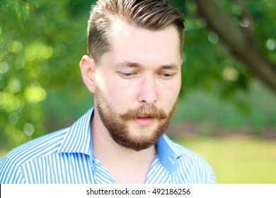 Closeup portrait of a bearded man in a shirt.