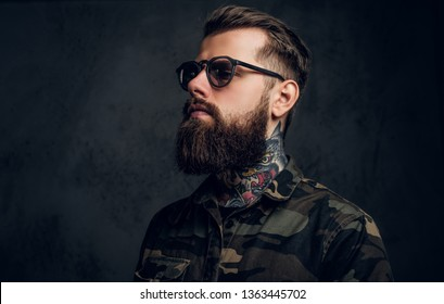 Closeup portrait of a bearded man with a tattoo on his neck in sunglasses wearing a military shirt. Studio photo against a dark wall