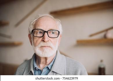 close-up portrait of bearded senior man in eyeglasses