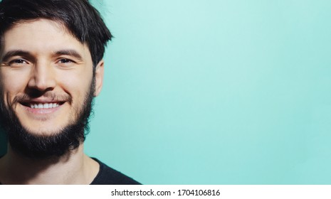 Close-up portrait of bearded smiling guy on cyan, aqua menthe color background with copy space.