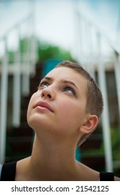 Close-up portrait of a beautful teenager girl looking upside and thinking. Stairs on the background