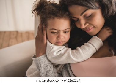Close-up portrait of beautiful african american mother and daughter hugging at home