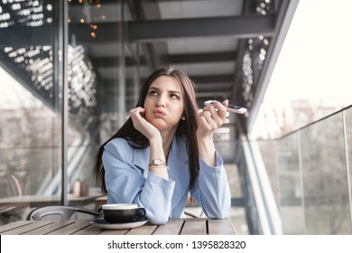 Closeup portrait of a beautiful annoyed woman holding phone to side, not listening to conversation girl wearing formal blue suit sitting at a table on cafe terrace balcony outside staircase background