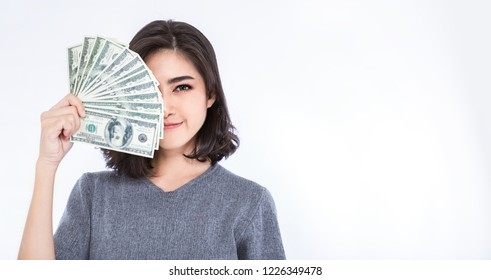 Closeup portrait of beautiful asian woman holding money half face. Pretty asian girl counting her salary dollar note. Success wealth financial business cashflow currency payment bill concept.