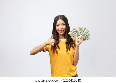 Closeup portrait of beautiful asian woman holding money isolated on white background. Asian girl counting her salary dollar note. Success wealth financial business cashflow currency payment concept