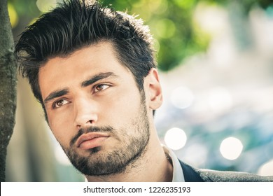 Close-up portrait of a beautiful and attractive man with a beard and trendy hair, bright eyes and dreamy expression. Outdoors with daylight.