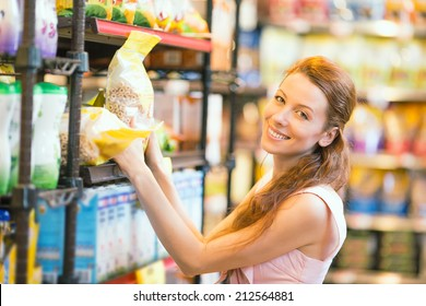 Closeup portrait Beautiful attractive young, happy, smiling Woman shopping for cereal, bulk in grocery supermarket. Positive facial expressions, emotions, feelings. Customer satisfaction concept