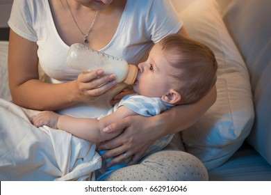 Closeup portrait of beautiful baby boy drinking milk from bottle in bed at night