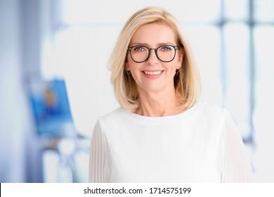 Nahaufnahme des Porträts einer schönen blonden Geschäftsfrau, die im Büro steht, während sie die Kamera anschaut und lächelt.