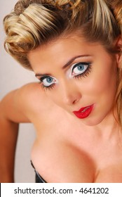Close-up portrait of beautiful blond female with blue eyes and red lips