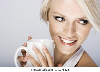 Close-up portrait of a beautiful blond woman smiling and holding a mug while looking back