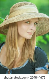 close-up portrait of beautiful blond woman wearing hat standing in park