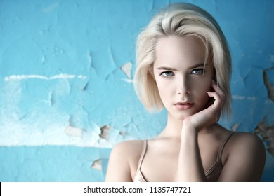 Close-up portrait of a beautiful blonde woman with nude makeup. Beauty, fashion concept. Make-up and cosmetics. Haircuts for short hair.