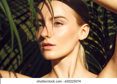 Close-up portrait of beautiful blonde young woman with perfect skin, beautiful green eyes and long neck hiding under palm leaf