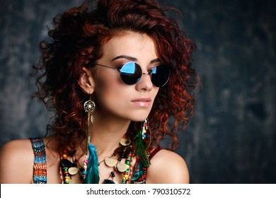 Close-up portrait of a beautiful bright woman with curly foxy hair in sunglasses, earrings and beads. Ethnic style in accessories.