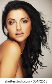 Close-up portrait of a beautiful brunet model in studio on light background